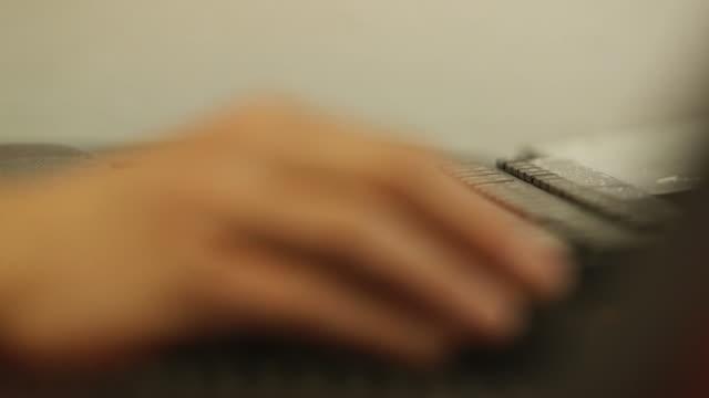 Man types on computer keyboard, close up