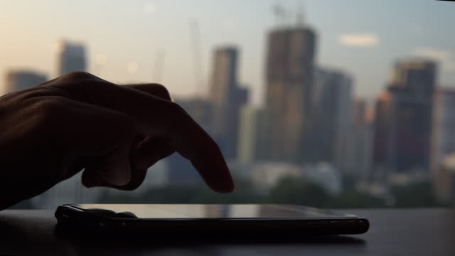 Man Typing a Message Using Mobile Phone and credit card and city view