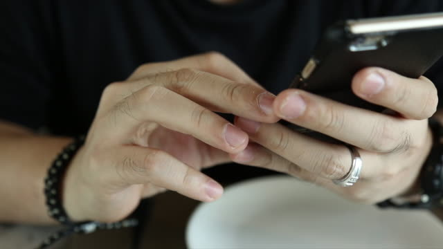 Man Typing a Message Using Mobile Phone in restaurant