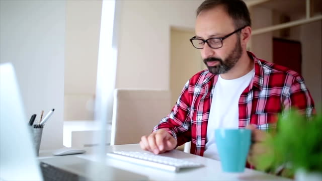Man typing on a computer at home
