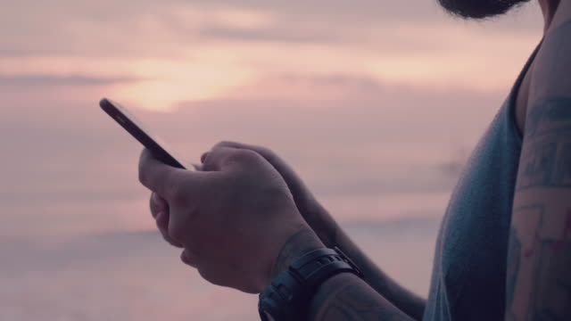 Man typing on smartphone by sea at sunset