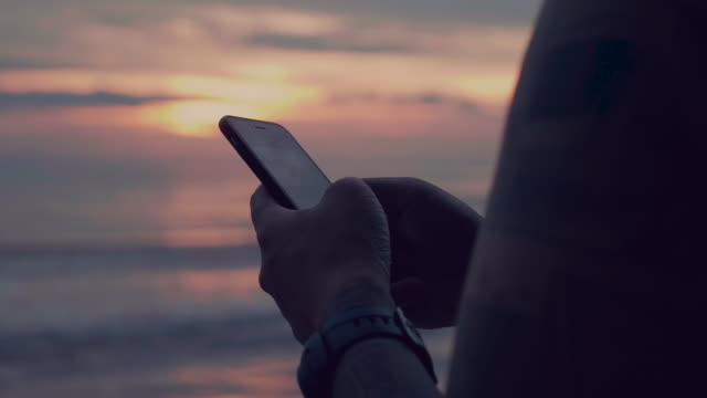 man typing on smartphone by sea at sunset - typing stock videos & royalty-free footage