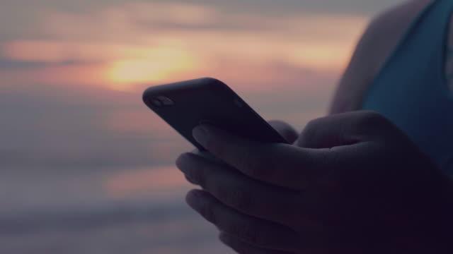 Man att skriva på smartphone sjövägen vid solnedgången