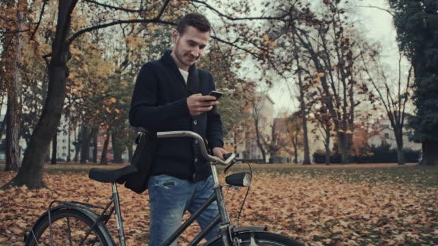 Man typing sms while pushing a bicycle