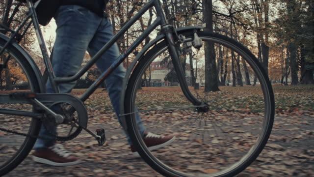Man typing sms while pushing his bicycle