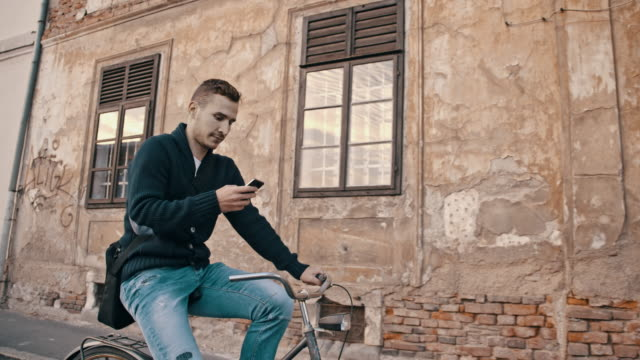 SLO MO Mann Schreiben von SMS während Sie auf einem Fahrrad