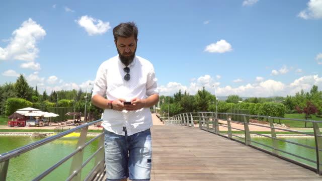 橋の上を歩きながら SMS を入力する男