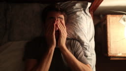 Man unable to sleep rubs his eyes and gets out of bed after having taken a nap