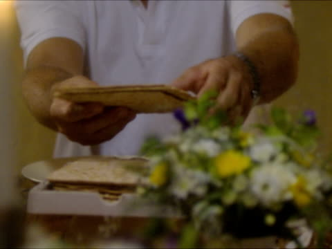 cu man uncovering and breaking matzo bread at seder night during passover dinner and ceremony / beit yitzhak, israel - passover stock videos and b-roll footage