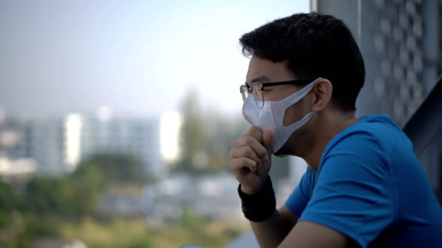 man under air pollution mask coughing because dusk pm 2.5 in the air around thechiang mai city, thailand - asian man coughing stock videos & royalty-free footage