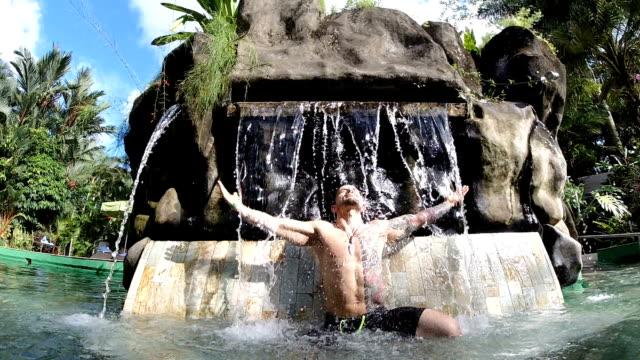 man under waterfall in outdoor pool - thermal pool stock videos & royalty-free footage