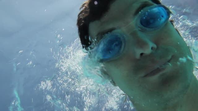 cu man underwater swimming and blowing bubbles at camera / golf de son termes, bunyola, mallorca, baleares, spain - swimming goggles stock videos & royalty-free footage
