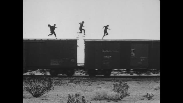 1918 man (fatty arbuckle) unhooks the caboose from the train and thinks he has escaped from the men chasing him, but the train reverses and bumps into the caboose - wild west stock videos & royalty-free footage