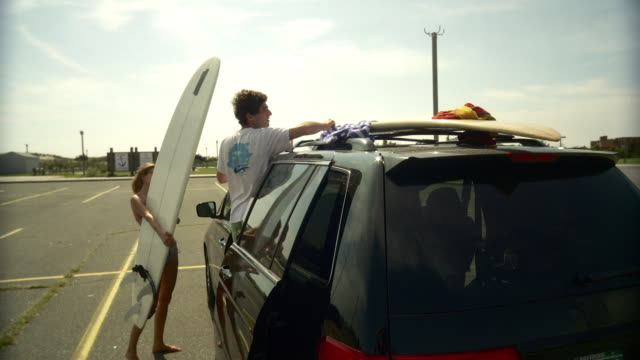 ws pan  man unloading surfboards off roof rack on parking lot / long beach, new york state, usa - entladen stock-videos und b-roll-filmmaterial