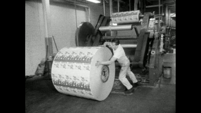 man unloads printed paper rolls from large press; 1964 - printing out stock videos & royalty-free footage