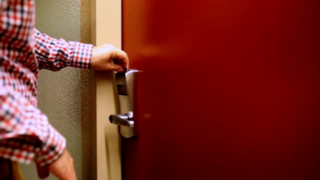 Man unlocks the door of the hotel room card