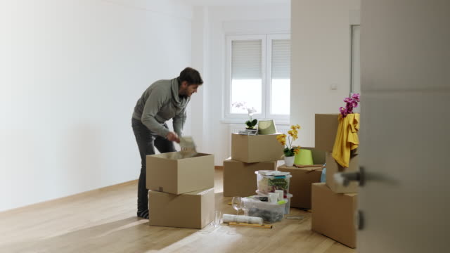 man unpacking cardboard box in his new apartment - adult student stock videos & royalty-free footage