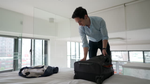 man unpacking his suitcase - loft apartment stock videos & royalty-free footage