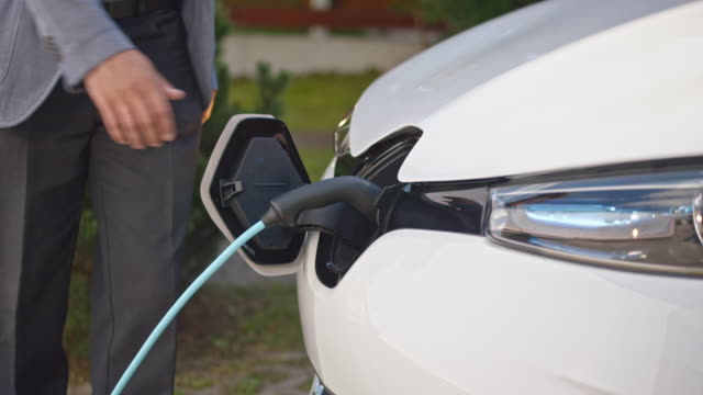 slo mo man unplugging electric car at home - plug socket stock videos and b-roll footage