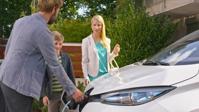 Man unplugging electric car before driving with family