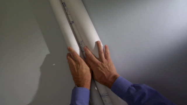 POV CU Man unrolling blueprint / Atlanta, Georgia, USA