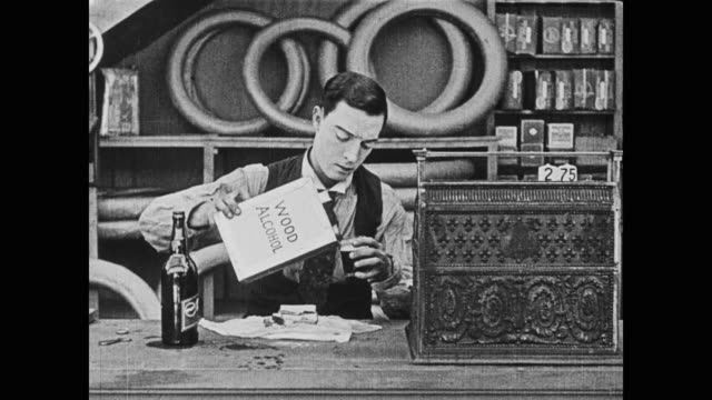 stockvideo's en b-roll-footage met 1920 man (buster keaton), unsatisfied with his soda, adds wood alcohol to it and likes the taste - proeven