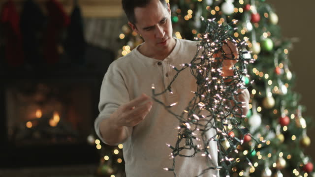 vídeos de stock e filmes b-roll de man untangling christmas tree lights - emaranhado
