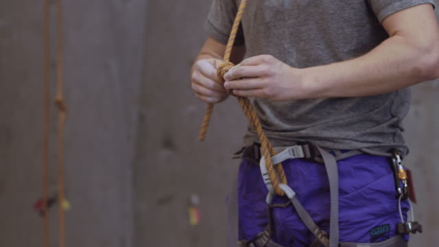 man untying knot in climbing rope - climbing wall stock videos & royalty-free footage