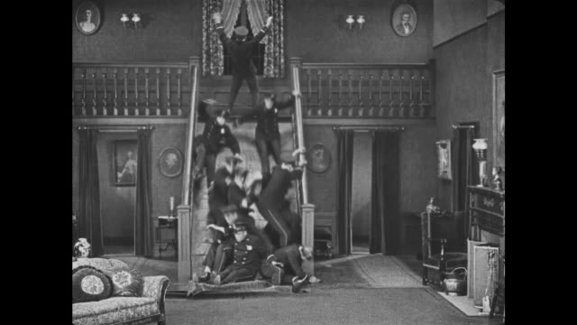 1921 man (joe roberts) unwittingly knocks crowd of policeman down the stairs as he explains to other man (edward f. cline) how his disappearing stairs controls work - 1921 stock-videos und b-roll-filmmaterial