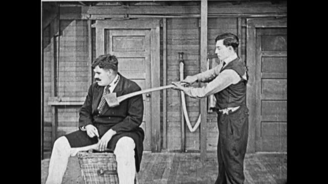 1919 man (buster keaton), upset at a strongman's treatment of his assistant, hits the strongman's head with the backside of an ax, and then the front side, but it doesn't harm him, and the strongman (charles a. post) pushes keaton - スラップスティックコメディ点の映像素材/bロール
