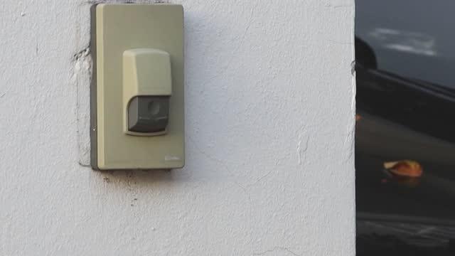 4k、男は家の中で呼び出し人のためのドアを押す指を使用します - 鳴る点の映像素材/bロール