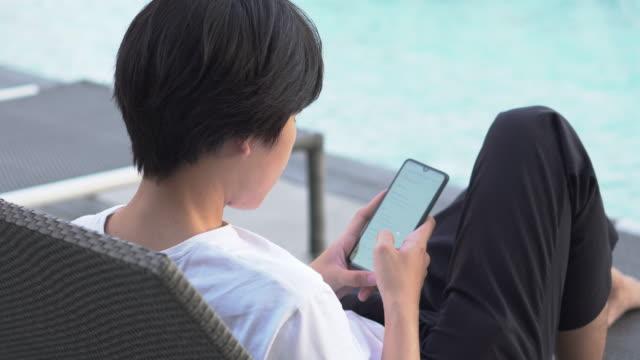 en man använder smartphone vid poolen - utebassäng bildbanksvideor och videomaterial från bakom kulisserna