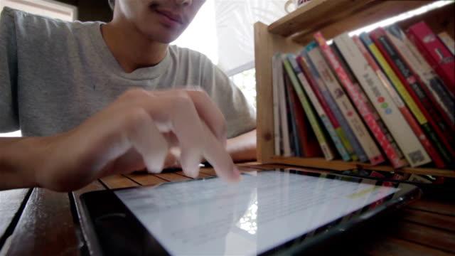 vídeos y material grabado en eventos de stock de hombre uso tableta en una cafetería - dispositivo de entrada