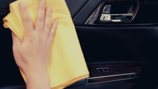Man use the yellow microfiber cloth to wipe clean the door console, the interior of the car is a beautiful black leather, 4k 30fps resolution.