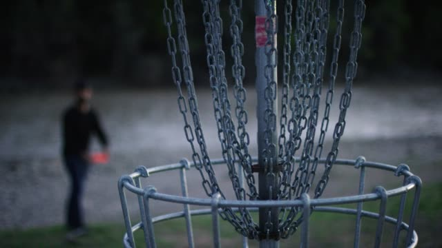 vídeos de stock e filmes b-roll de a man uses a backhand putt to throw a disc golf putter into a disc golf basket in an uncultivated outdoor area next to the colorado river at a disc golf course at sunset (frisbee golf) - golf