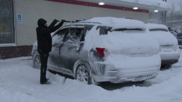 a man uses a brush to clear snow from his vehicle in adams new york after several feet of snow fell on the area during a heavy lake effect snowstorm - scott mcpartland stock videos & royalty-free footage