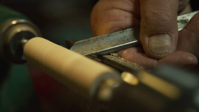 en man använder en mejsel för att forma en roterande dowel av trä av en svarv - skicklighet bildbanksvideor och videomaterial från bakom kulisserna