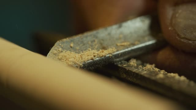 A Man Uses a Chisel to Shape a Rotating Dowel of Wood of a Lathe