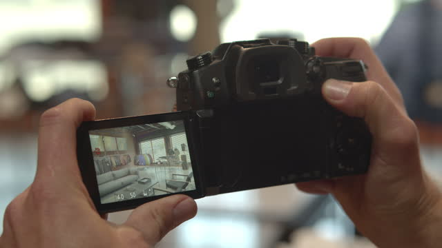 man uses a digital camera to take pictures inside a retail space, day - photography themes stock videos & royalty-free footage