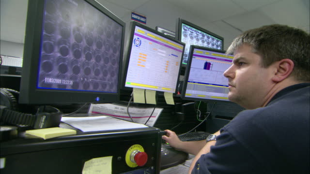 A man uses a joystick as he controls a camera and watches tube channels on a computer screen.
