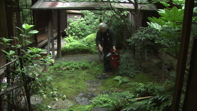 A man uses a ladle to splash water on stepping stones in a garden.