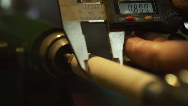 a man uses a micrometer to measure the thickness of a wooden dowel on a lathe - skill stock videos & royalty-free footage