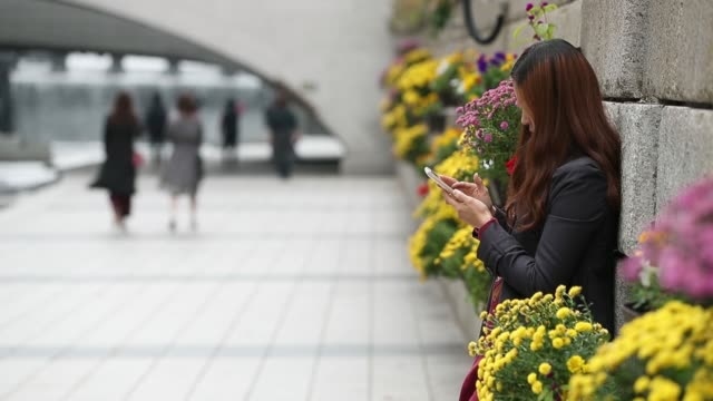 A man uses a mobile device as he leans on a railing near the Cheonggyecheon stream in Seoul South Korea on Wednesday Oct 26 A man plays a chess game...
