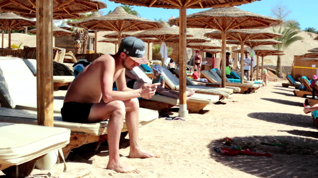 man uses a mobile phone to work while on holiday in egypt. sharm el-sheikh. - red sea stock videos & royalty-free footage