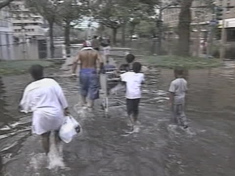 man uses a shopping cart to get his family through floodwaters caused by hurricane katrina. - survival stock videos & royalty-free footage