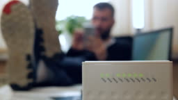 A man uses a smartphone in the office with his legs folded on the table. Wireless router. Medium shot