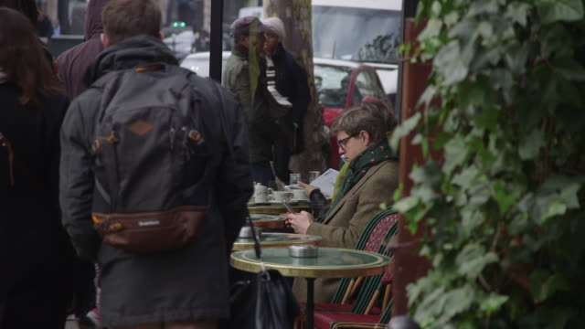 a man uses a smartphone whilst sitting outside the cafe de flore in saintgermaindesprés paris france rushes taken from bbccom/culture absa734n - stereotypical stock videos & royalty-free footage