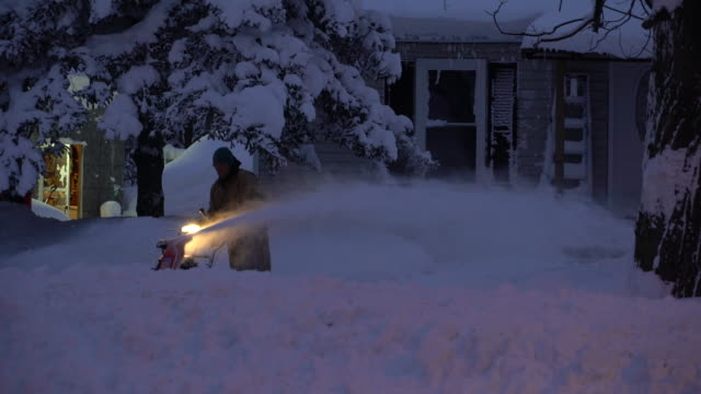 A man uses a snow blower to clear his driveway of deep snow in the wake of a record breaking lake effect snow storm in Upstate New York