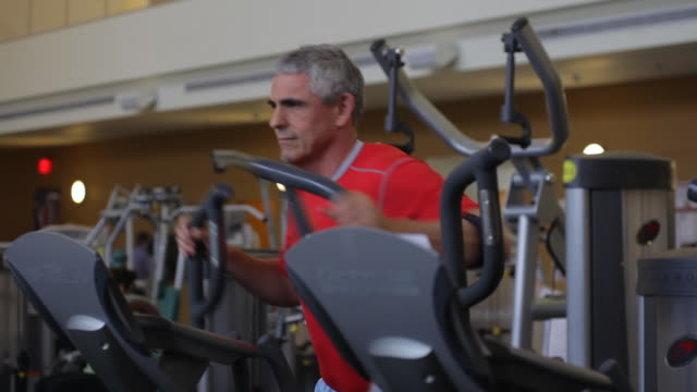 a man uses an elliptical machine to get in shape. - cross trainer stock videos and b-roll footage