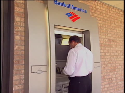 a man uses an outdoor bank of america atm machine - bank of america stock videos & royalty-free footage